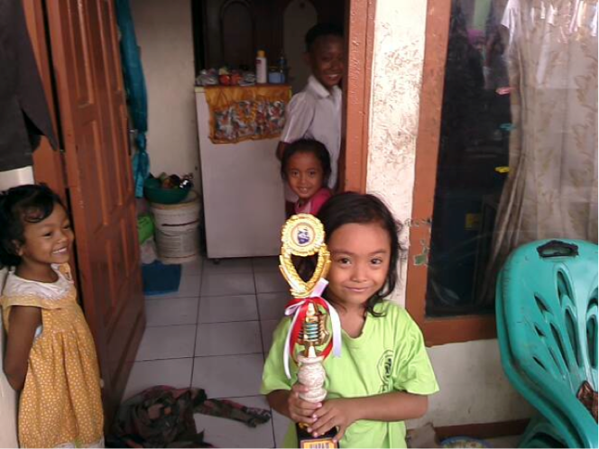 A child from the neighbourhood proudly showed her trophy of coloring competition. She is happy to get lesson from the Dutasia Learning Post. Credits: Henri Uranus