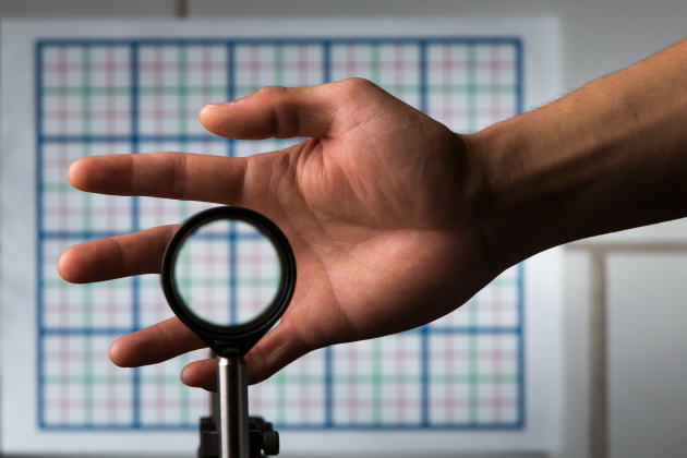 A multidirectional `perfect paraxial' cloak using 4 lenses. For a continuous range of viewing angles, the hand remains cloaked, and the grids seen through the device match the background on the wall (about 2 m away), in color, spacing, shifts, and magnification. The edges of the optics can be seen since this is a small-angle ('paraxial') cloak, but this can be reduced by using large optics and for distant viewing; also the center of the device must not be blocked.  Credit: J. Adam Fenster / University of Rochester