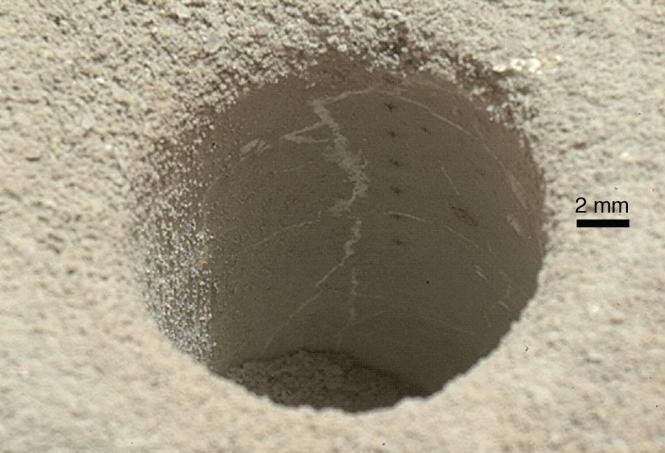 ChemCam laser analysis pits form a line inside the hole drilled by the Curiosity rover in the Sheepbed Mudstone. Each laser pit was produced by 30 laser shots, each with an energy of 14 milliJoules. The hole is about the size of a US dime and was shot from about 2.5 meters distance. Credit: NASA/JPL-Caltech/MSSS.