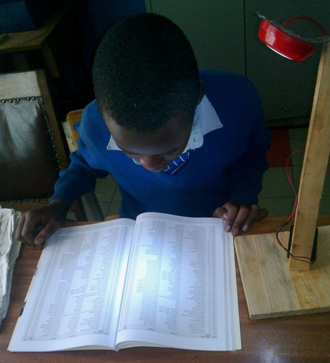 Student from Dagoretti Primary School Nairobi in Kenya reading using one of the mobile LED lanterns. Credit: Dieter Arnold.