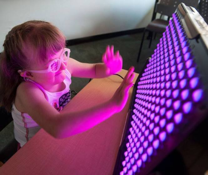 Alexis plays with LightAide. Credit: Perkins School for the Blind.