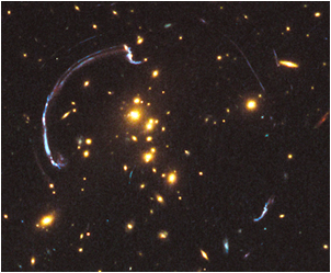 A striking example, made by the Hubble Space Telescope, of gravitational lensing, where the gravitational field of a foreground galaxy bends and amplifies the light of a distant background galaxy. Image credit: NASA, ESA, J. Rigby, K. Sharon, M. Gladders, E. Wuyts.