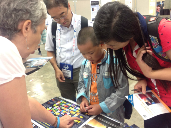 A young visitor at the Honolulu Convention Centre, host venue of the IAU XXIX General Assembly learns that fighting light pollution can be fun. Credit: IAU OAO/ Lina Canas.
