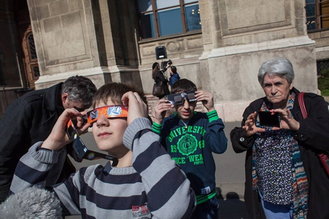 Watching a solar eclipse in front of the headquarters of MTA in Széchenyi tér, Budapest. Credit: the Roland Eötvös Physical Society.