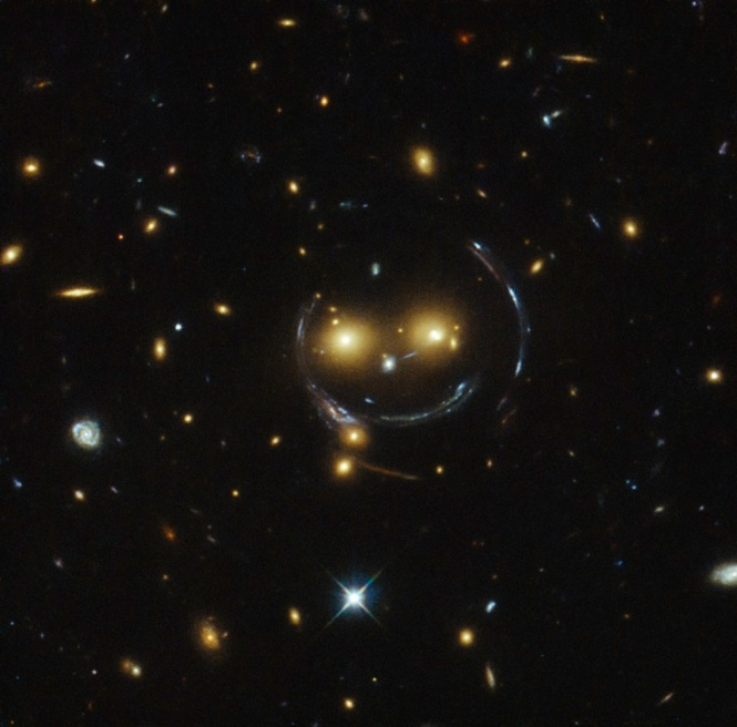 """In the centre of this image there are two faint galaxies that seem to be smiling. You can make out two orange eyes and a white button nose. In the case of this """"happy face"""", the two eyes are the galaxies SDSSCGB 8842.3 and SDSSCGB 8842.4 and the misleading smile lines are actually arcs caused by an effect known as strong gravitational lensing. Credit: NASA/ESA Hubble Space Telescope."""