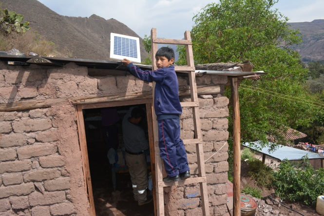 Aníbal Huamán Choque, second-grade student helping with the installation of the solar panel on his home. Credit: Fundación Niños del Arco Iris.